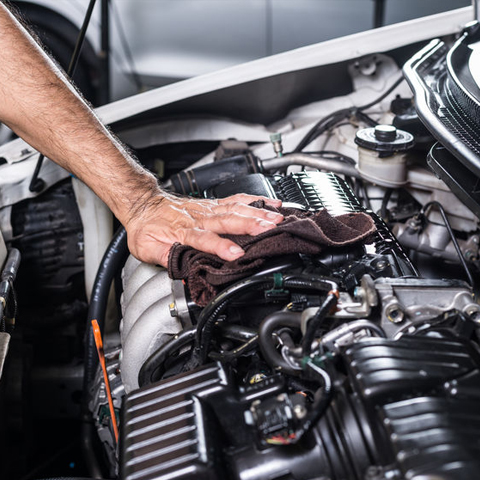 Man wiping engine down after inspection